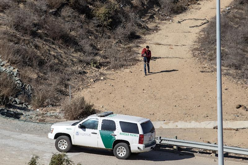 A man with a child in his arms walks toward a US patrol after illegally crossing the US-Mexico border (AFP Photo/Guillermo Arias)