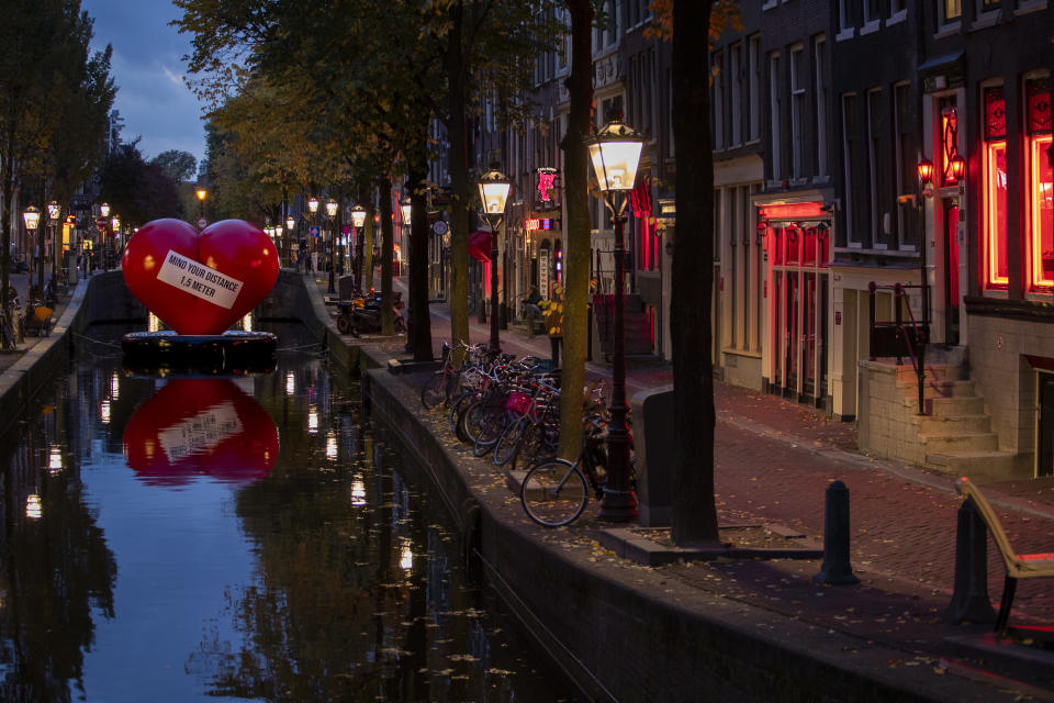 A red heart carries a social distancing message in a near-empty Red Light District in Amsterdam, Netherlands, Friday, Oct. 23, 2020. (AP Photo/Peter Dejong)