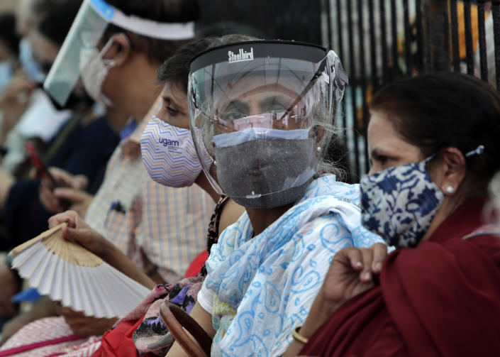 People wearing face shields and masks as a precaution against the coronavirus as they wait to receive COVID-19 vaccine in Mumbai, India, Thursday, April 29, 2021. India set another global record in new virus cases Thursday, as millions of people in one state cast votes despite rising infections and the country geared up to open its vaccination rollout to all adults amid snags. (AP Photo/Rajanish Kakade)