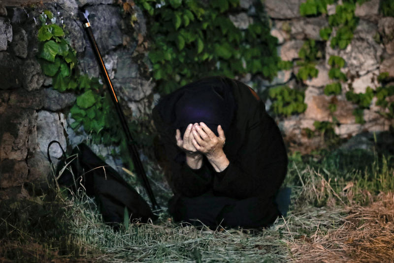 An orthodox worshiper kneels during a religious service in the Black Sea port of Constanta, Romania, late Tuesday, May 26, 2020. (AP Photo/Vadim Ghirda)