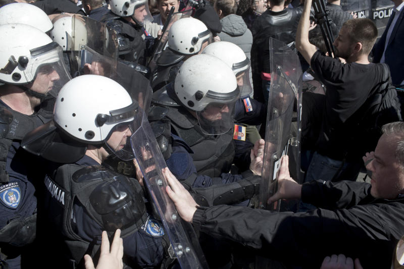 Riot police clash with protesters in Belgrade, Serbia, Sunday, March 17, 2019. As Serbian president Aleksandar Vucic held a news conference in the presidency building in downtown Belgrade, thousands of opposition supporters gathered in front demanding his resignation. Skirmishes with riot police were reported, including officers firing tear gas against the protesters who have pledged to form a human chain around the presidency to prevent Vucic from leaving the building. (AP Photo/Marko Drobnjakovic)