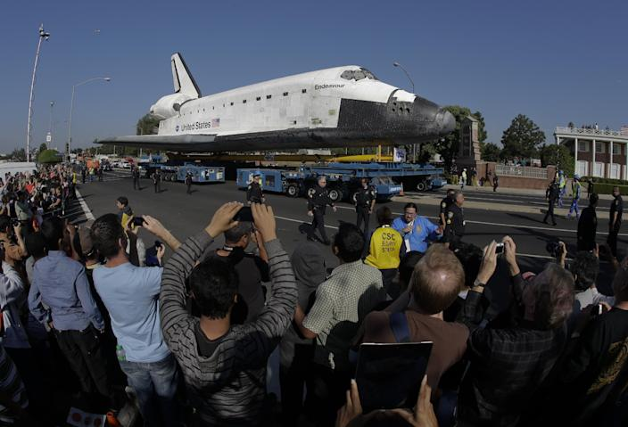 On lookers watch as he space shuttle Endeavour makes it's way down Manchester Blvd. in Inglewood, Calif., Saturday, Oct. 13, 2012. Endeavour's 12-mile road trip kicked off shortly before midnight Thursday as it moved from its Los Angeles International Airport hangar en route to the California Science Center, its ultimate destination. (AP Photo/Chris Carlson)