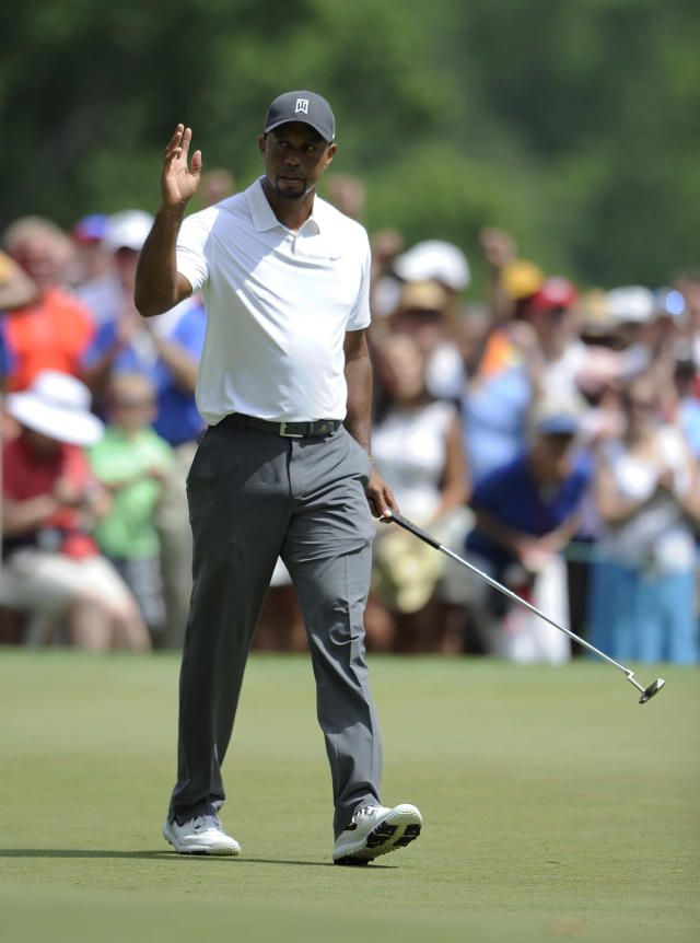 Tiger Woods waves to the gallery on the ninth green during the second round of the Quicken Loans National golf tournament, Friday, June 27, 2014, in Bethesda, Md. (AP Photo/Nick Wass)