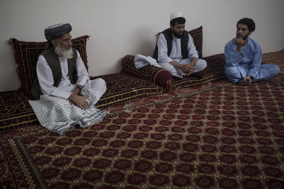 Ghulam Ghous, left, sits with his sons Ghulam Zikria, center, and Zakir Anwari, in their home in Kabul, Afghanistan, Friday, Sept. 17, 2021. Ghous lost his other son Zaki Anwari, a 17-year-old soccer player, who died after trying to board a U.S. Air Force C-17 taking off from Kabul's International Airport last month. (AP Photo/Felipe Dana)