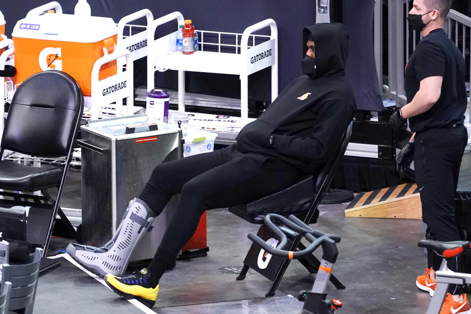 LeBron James sits in a chair near the bench area wearing black sweats with his hoodie pulled over his head and a black facemask with a walking boot on his right foot.