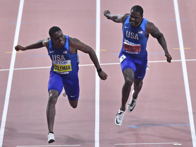 Christian Coleman, of the United States, left, crosses the finish line to win the men's 100 meter race ahead of silver medalist Justin Gatlin, of the United States, right, during the World Athletics Championships in Doha, Qatar, Saturday, Sept. 28, 2019. (AP Photo/Martin Meissner)