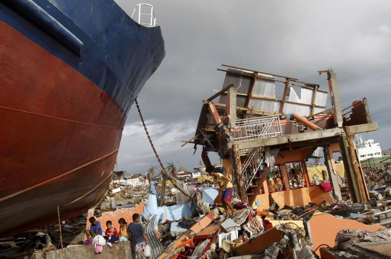 Survivors do their laundry at a well next to a ship that washed ashore in their destroyed community after the Super typhoon Haiyan battered Tacloban city