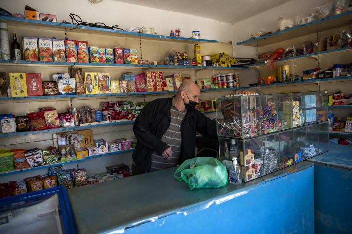 "Kosovo Albanian Fadil Rama choses products from his shop to be sent to a Kosovo Serb Blagica Dicic a lonely 92-year old woman in a remote village of Vaganesh, Kosovo on Thursday, Nov. 19, 2020, abandoned by all her former ethnic Serb neighbors. Neighbor Blagica Dicic, is 92 and in failing health, in the remote ethnic Serb minority village in the mountains of eastern Kosovo but Fadil Rama comes from the other side of Kosovo's bitter ethnic divide, being a member of Kosovo's ethnic Albanian majority and Rama said he saw nothing strange in helping an elderly Serb. ""I will never leave her on her own,"" he said. (AP Photo/Visar Kryeziu)"