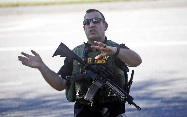 <p>A law enforcement officer tells anxious family members to move back, Wednesday, Feb. 14, 2018, in Parkland, Fla. A shooting at Marjory Stoneman Douglas High School sent students rushing into the streets as SWAT team members swarmed in and locked down the building. Police were warning that the shooter was still at large even as ambulances converged on the scene and emergency workers appeared to be treating those possibly wounded. (Photo: Wilfredo Lee/AP) </p>