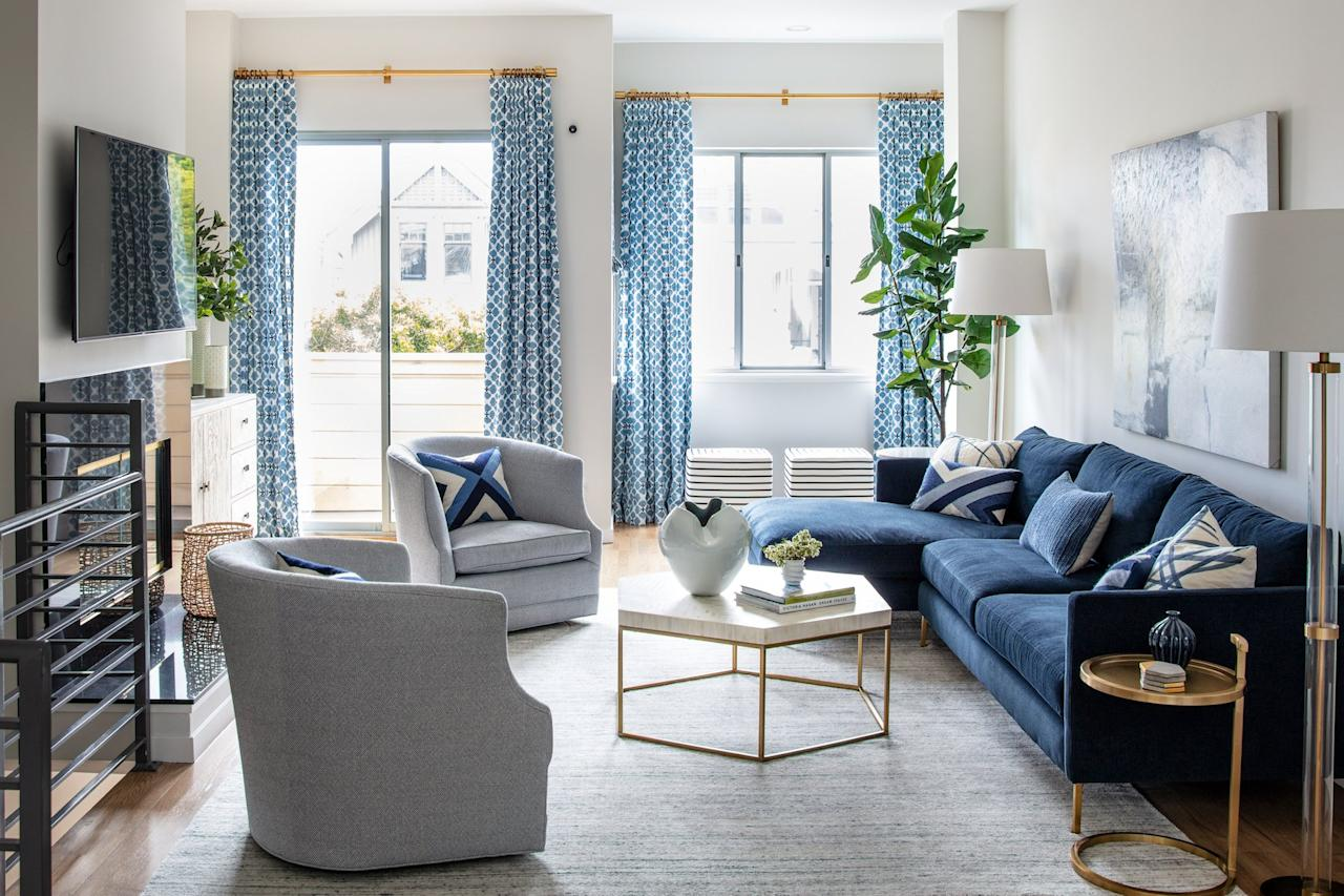 """<p>In the gorgeous living room, a mix of pattern pops on the curtains and throw pillows. """"We love mixing patterns!,"""" says Laura Williams. And while she assures us that there aren't many rules to follow, there are a few guidelines that can help when introducing patterns. Tip #1: """"We usually like to mix a bigger scale pattern with a smaller scale pattern."""" With a smaller scale on the window treatments and a larger scale on the pillows, the patterns play nicely in the same space. </p>"""
