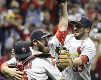 Jason Motte is surrounded by teammates Yadier Molina (left) and Daniel Descalso after recording the final out of the NLCS on Sunday