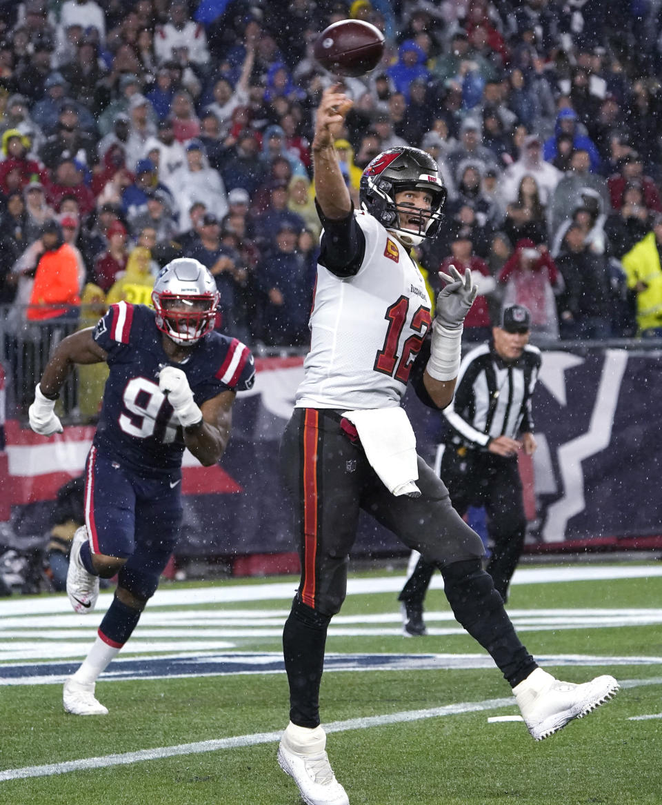 Tampa Bay Buccaneers quarterback Tom Brady (12) throws a pass while New England Patriots defensive end Deatrich Wise (91) gives chase during the first half of an NFL football game, Sunday, Oct. 3, 2021, in Foxborough, Mass. (AP Photo/Elise Amendola)