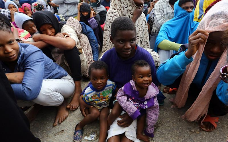 African migrants sit at a gathering at the Tripoli branch of the Anti-Illegal Immigration Authority, in the Libyan capital - Credit: AFP