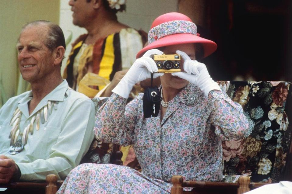 The Queen taking photographs during her visit to the South Sea islands of Tuvalu in 1982 (Ron Bell/PA) (PA Archive)