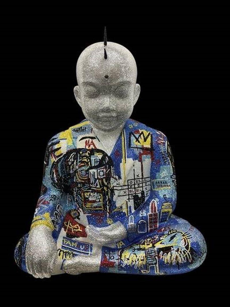 A statue of Buddha covered in pop art.
