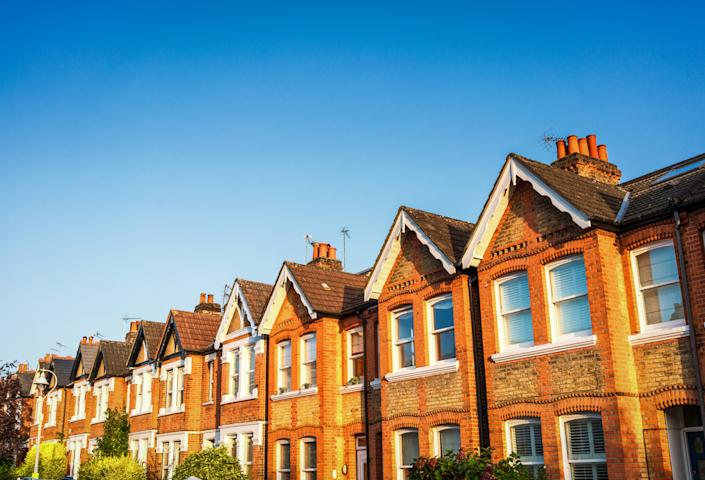 A long row of traditional Victorian terraced houses in Ealing, West London, below a clear blue summer sky.