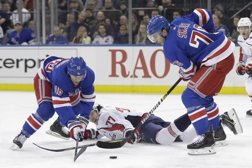 Washington Capitals' T.J. Oshie (77) fights for control of the puck with New York Rangers' Brady Skjei (76) and Ryan Strome (16) during the first period of an NHL hockey game Wednesday, Nov. 20, 2019, in New York. (AP Photo/Frank Franklin II)