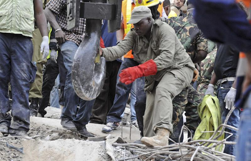 A rescuer guides the hook of a crane as it prepares to remove pieces of rubble from a collapsed building in downtown Dar es Salaam, Tanzania Friday, March 29, 2013. A Tanzanian police official says the multi-storey building was in the final stages of its construction and most of the people caught up in the collapse were passing by. (AP Photo/Khalfan Said)