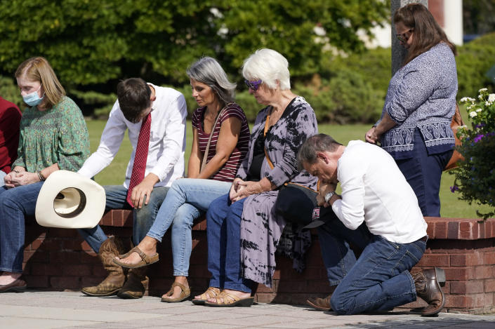 People pray during a vigil at the Collierville Town Hall, Friday, Sept. 24, 2021, in Collierville, Tenn. The vigil is for the person killed and those injured when a gunman attacked people in a Kroger grocery store Thursday before he was found dead of an apparent self-inflicted gunshot wound. (AP Photo/Mark Humphrey)
