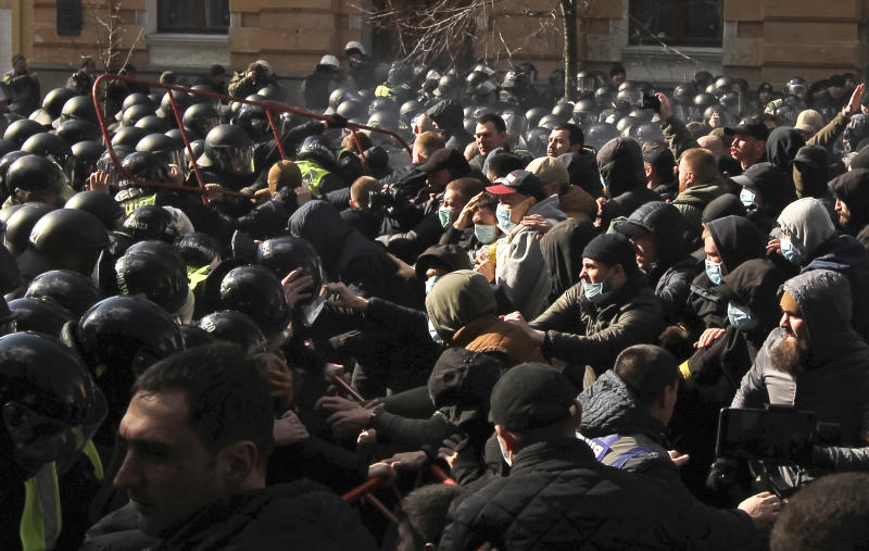Far-right demonstrators clash with riot police outside the presidential administration building in Kiev, Ukraine, Saturday, March 9, 2012. Three police officers in Ukraine have been injured in a clash with far-right demonstrators in the capital. The violence occurred outside the presidential administration building in Kiev where several hundred demonstrators had gathered Saturday to call for arrests of top figures in an alleged military corruption scandal. (AP Photo/Vladimir Donsov)