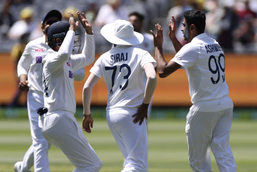 India's Ravichandran Ashwin, right, is congratulated by teammates after taking the wicket of Australia's Steve Smith for no score during play on day one of the Boxing Day cricket test between India and Australia at the Melbourne Cricket Ground, Melbourne, Australia, Saturday, Dec. 26, 2020. (AP Photo/Asanka Brendon Ratnayake)
