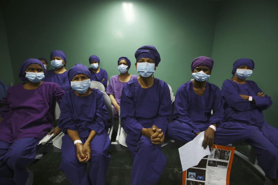 """Nepalese patients wait to receive anesthesia before eye surgery at the Tilganga Eye Center in Kathmandu, Nepal, Friday, March 26, 2021. Nepal's """"God of Sight"""" eye doctor renowned for his innovative and inexpensive cataract surgery for the poor is taking his work beyond the Himalayan mountains to other parts of the world so there is no more unnecessary blindness in the world. Dr. Sanduk Ruit, who has won many awards for his work and performed some 130,000 cataract surgery in the past three decades, is aiming to expand his work beyond the borders of his home country and the region to go globally. (AP Photo/Niranjan Shrestha)"""