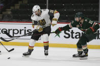 Minnesota Wild's Carson Soucy (21) and Vegas Golden Knights' Nicolas Roy (10) go after the puck in the second period of an NHL hockey game Monday, March 8, 2021, in St. Paul, Minn. (AP Photo/Stacy Bengs)
