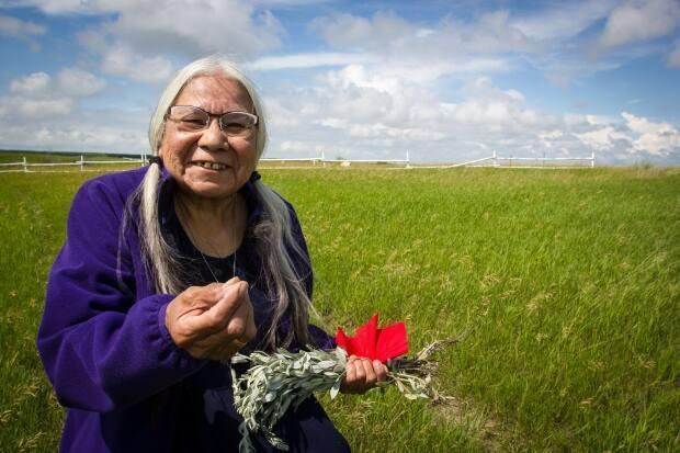 Kokum standing where her family home once stood on Peepeekisis First Nation in southern Saskatchewan, holding sage.