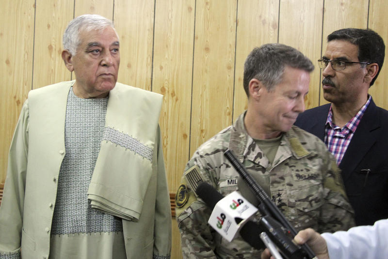 Kandahar Gov. Zalmay Wesa, left, stands with the head of NATO troops in Afghanistan, Gen. Scott Miller, center, and a translator, during a meeting, in Kandahar, Afghanistan, Thursday, Oct. 18, 2018. The three top officials in Afghanistan's Kandahar province were killed, including Wesa, when their own guards opened fire on them at the security conference Thursday, the deputy provincial governor said. A Taliban spokesman said the target was Miller, who escaped without injury, according to NATO. (AP Photo)