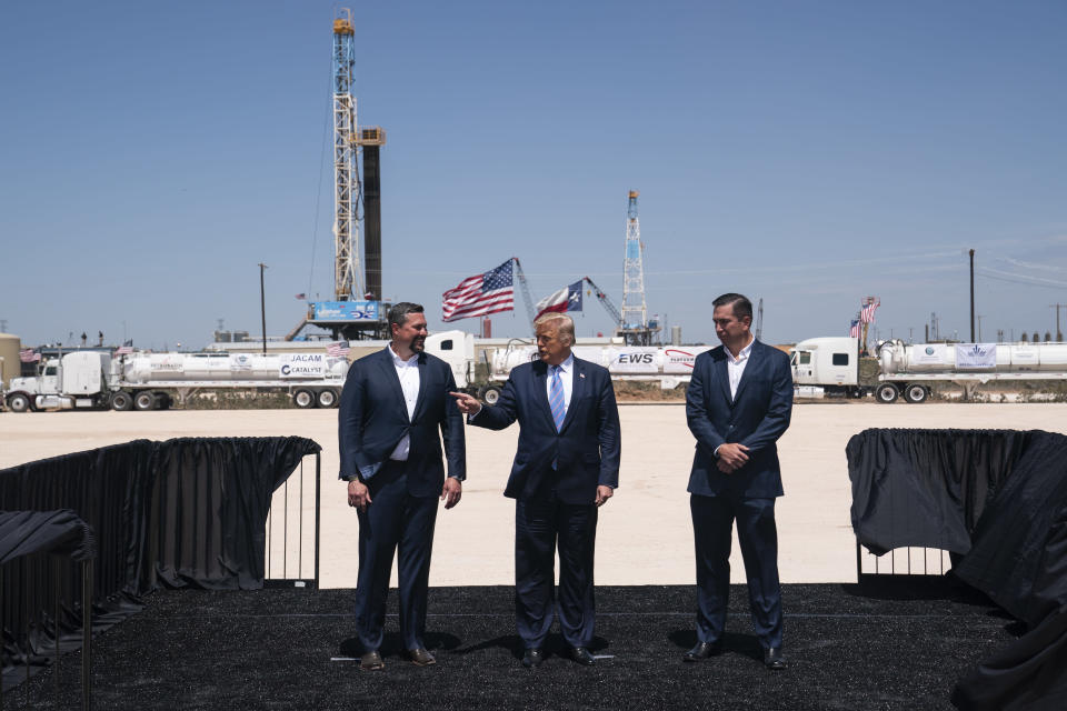 President Donald Trump stands with Double Eagle Energy co-CEOs Cody Campbell, left, and John Sellers, right, as he arrives at the Double Eagle Energy Oil Rig, Wednesday, July 29, 2020, in Midland, Texas. (AP Photo/Evan Vucci)