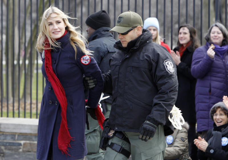 Actress Daryl Hannah is arrested outside the White House in Washington, Wednesday, Feb. 13, 2013, as prominent environmental leaders tied themselves to the White House gate to protest the Keystone XL oil pipeline.. (AP Photo/Ann Heisenfelt)