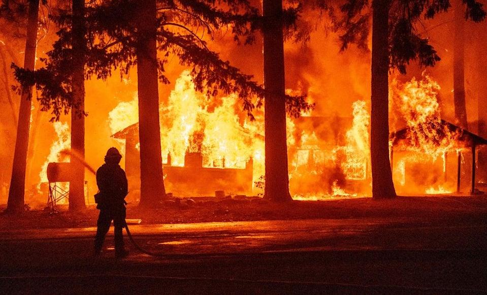 A firefighter sprays water on a propane tank as a home burns due to the Dixie fire in California (AFP via Getty Images)
