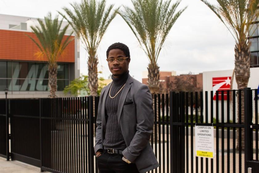 "Stevie Carpenter, a graduate of L.A. City College, stands in front of the closed campus. Carpenter is planning to transfer to UC Davis this fall, but his withdrawal from an online class could put those plans in jeopardy. <span class=""copyright"">(Gabriella Angotti-Jones/Los Angeles Times)</span>"