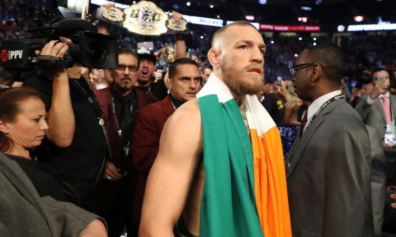 Conor McGregor with an Irish flag draped over his shoulders.