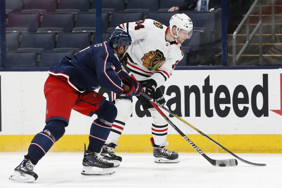 Chicago Blackhawks' Carl Soderberg, right, carries the puck as Columbus Blue Jackets' Seth Jones defends during the first period of an NHL hockey game Thursday, Feb. 25, 2021, in Columbus, Ohio. (AP Photo/Jay LaPrete)