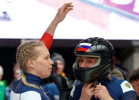 FILE PHOTO: Russia's pilot Olga Stulneva (L) looks at teammate Liudmila Udobkina as she takes off her helmet after completing a run in the women's bobsleigh event at the 2014 Sochi Winter Olympics, at the Sanki Sliding Center in Rosa Khutor February 19, 2014. REUTERS/Arnd Wiegmann/File Photo