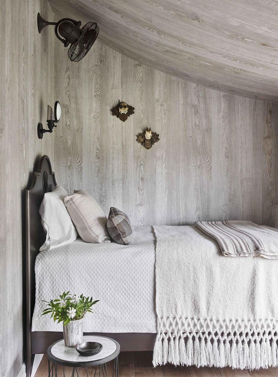 """<p>In this Low Country home designed by Beth Webb, a cozy guest nook—one of three bedrooms tucked on the second floor—reveals the soft swoop of the roof clad with a faux-bois wallcovering (<a href=""""https://nobilis.fr/en/"""" rel=""""nofollow noopener"""" target=""""_blank"""" data-ylk=""""slk:Nobilis"""" class=""""link rapid-noclick-resp"""">Nobilis</a>). """"It's like sleeping under a tent, which is fitting out in the country,"""" says <a href=""""https://www.peterblockarchitects.com/"""" rel=""""nofollow noopener"""" target=""""_blank"""" data-ylk=""""slk:architect Peter Block"""" class=""""link rapid-noclick-resp"""">architect Peter Block</a>. Sconce and fan, <a href=""""https://www.circalighting.com/"""" rel=""""nofollow noopener"""" target=""""_blank"""" data-ylk=""""slk:Circa Lighting"""" class=""""link rapid-noclick-resp"""">Circa Lighting</a></p>"""