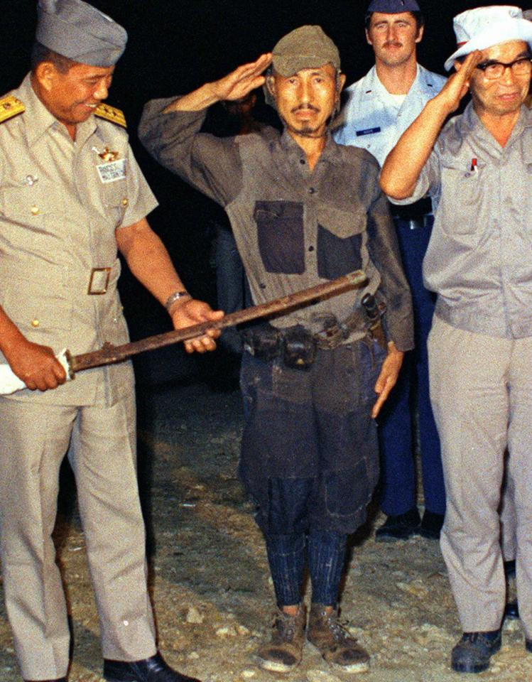 Hiroo Onoda (C) salutes after handing over a military sword on Lubang Island in northwestern Phillippines, in this Kyodo file photo taken March 1974. Onoda, a former Imperial Japanese Army intelligence officer who remained on the island for nearly 29 years without knowledge of Japan's surrender in World War II, died aged 91 at a Tokyo hospital on January 16, 2014. Mandatory credit. REUTERS/Kyodo/Files (PHILLIPPINES - Tags: CONFLICT POLITICS OBITUARY) ATTENTION EDITORS - FOR EDITORIAL USE ONLY. NOT FOR SALE FOR MARKETING OR ADVERTISING CAMPAIGNS. THIS IMAGE HAS BEEN SUPPLIED BY A THIRD PARTY. IT IS DISTRIBUTED, EXACTLY AS RECEIVED BY REUTERS, AS A SERVICE TO CLIENTS. MANDATORY CREDIT. JAPAN OUT. NO COMMERCIAL OR EDITORIAL SALES IN JAPAN. YES