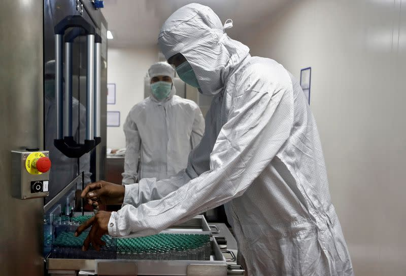 FILE PHOTO: An employee in personal protective equipment (PPE) removes vials of AstraZeneca's COVISHIELD, coronavirus disease (COVID-19) vaccine, from a visual inspection machine inside a lab at Serum Institute of India, Pune