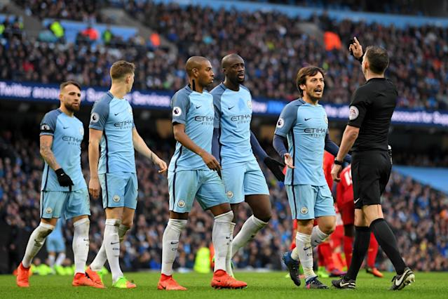 <p>Manchester City players surround Michael Oliver after the referee awards Liverpool a penalty </p>