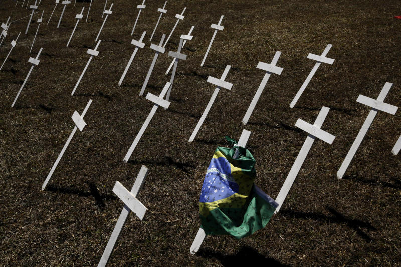 Rows of crosses representing the thousands of deaths due to the new coronavirus are displayed on a lawn during a protest demanding President Jair Bolsonaro be impeached, in front of the National Congress in Brasilia, Brazil, Tuesday, July 14, 2020. As Brazil careens toward a full-blown public health emergency and economic meltdown, opponents have filed a request for Bolsonaro's impeachment based on his mishandling of the new coronavirus pandemic. (AP Photo/Eraldo Peres)