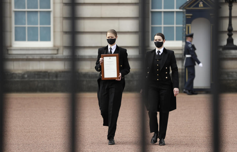 A member of staff carries an announcement, regarding the death of Britain's Prince Philip, to be displayed on the fence of Buckingham Palace in London, Friday, April 9, 2021. Buckingham Palace officials say Prince Philip, the husband of Queen Elizabeth II, has died. He was 99. Philip spent a month in hospital earlier this year before being released on March 16 to return to Windsor Castle. (AP Photo/Matt Dunham)