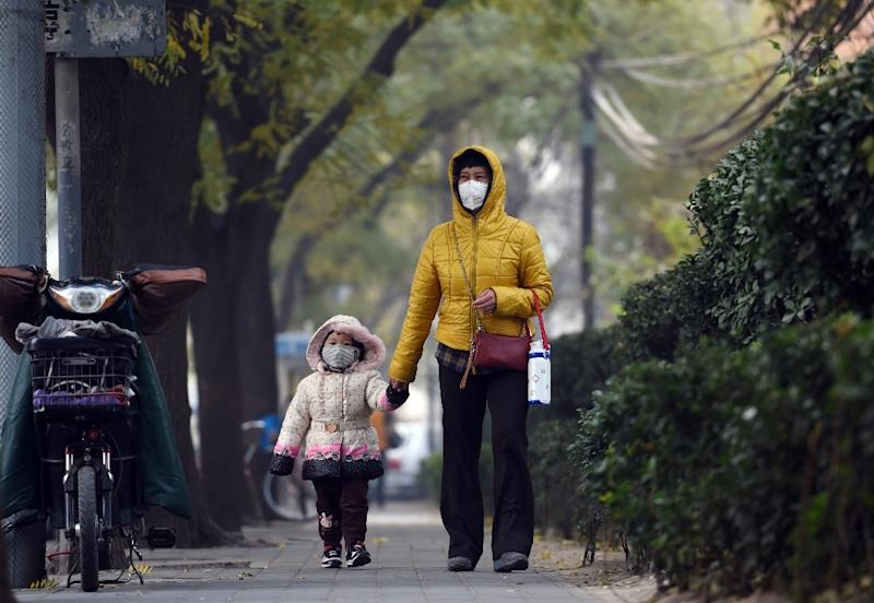 A woman and child wear masks on a polluted day in Beijing on November 26, 2014 (AFP Photo/Greg Baker)