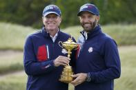 Team USA captain Steve Stricker and Team USA's Dustin Johnson hold the Ryder Cup during a practice day at the Ryder Cup at the Whistling Straits Golf Course Wednesday, Sept. 22, 2021, in Sheboygan, Wis. (AP Photo/Charlie Neibergall)