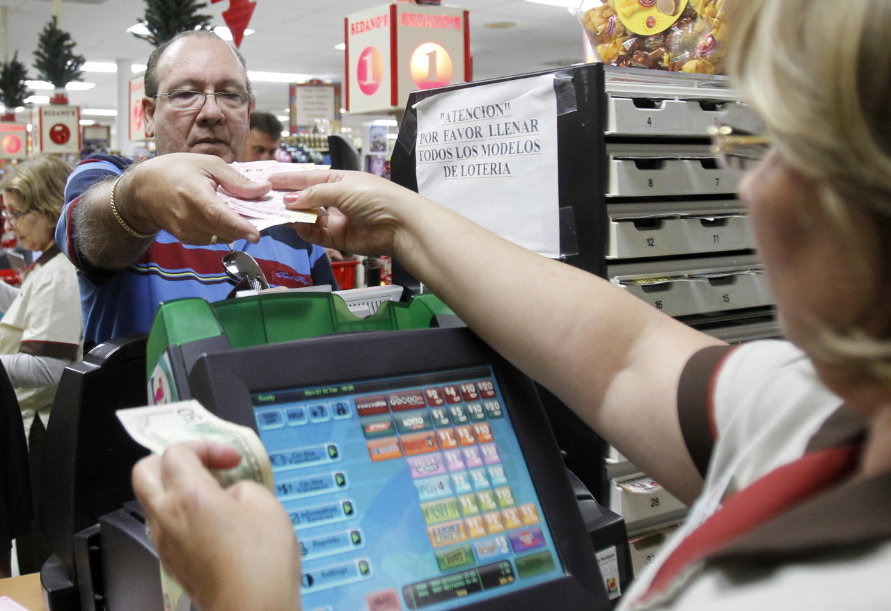 Maria Diaz, right, sells a customer Powerball tickets at a local supermarket in Hialeah, Fla.,Tuesday, Nov. 27, 2012. There has been no Powerball winner since Oct. 6, and the jackpot already has reached a record level for the game. Already over $500 million, it is the second-highest jackpot in lottery history, behind only the $656 million Mega Millions prize in March. (AP Photo/Alan Diaz)