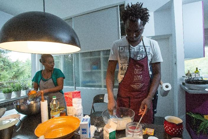 """David Ajobi (R), a 34-year-old medical student from Nigeria in Croatia, makes the popular """"agege"""" bread from his country, a recipe taught to him by his mother (AFP Photo/Damir Sencar)"""