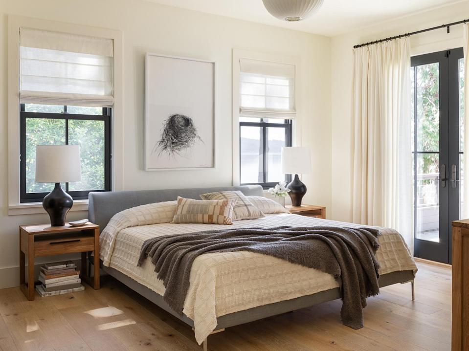 """<p>For the <a href=""""https://www.marthastewart.com/1125486/beautiful-bedroom-ideas"""" rel=""""nofollow noopener"""" target=""""_blank"""" data-ylk=""""slk:main bedroom"""" class=""""link rapid-noclick-resp"""">main bedroom</a>, Studio Ore softened the overarching high-contrast palette with calmer, balanced colors, seen here in the multiple wood tones, creamy white blankets, and varying shades of gray.</p>"""