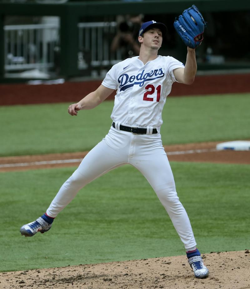 Dodgers starting pitcher Walker Buehler snags a bouncer by Atlanta's Nick Markakis.