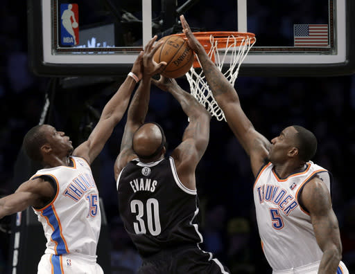 Both Oklahoma City Thunder's Reggie Jackson, left, and Kendrick Perkins, right, get a hand on a shot by Brooklyn Nets' Reggie Evans during the first half of an NBA basketball game Friday, Jan. 31, 2014, in New York. (AP Photo/Seth Wenig)
