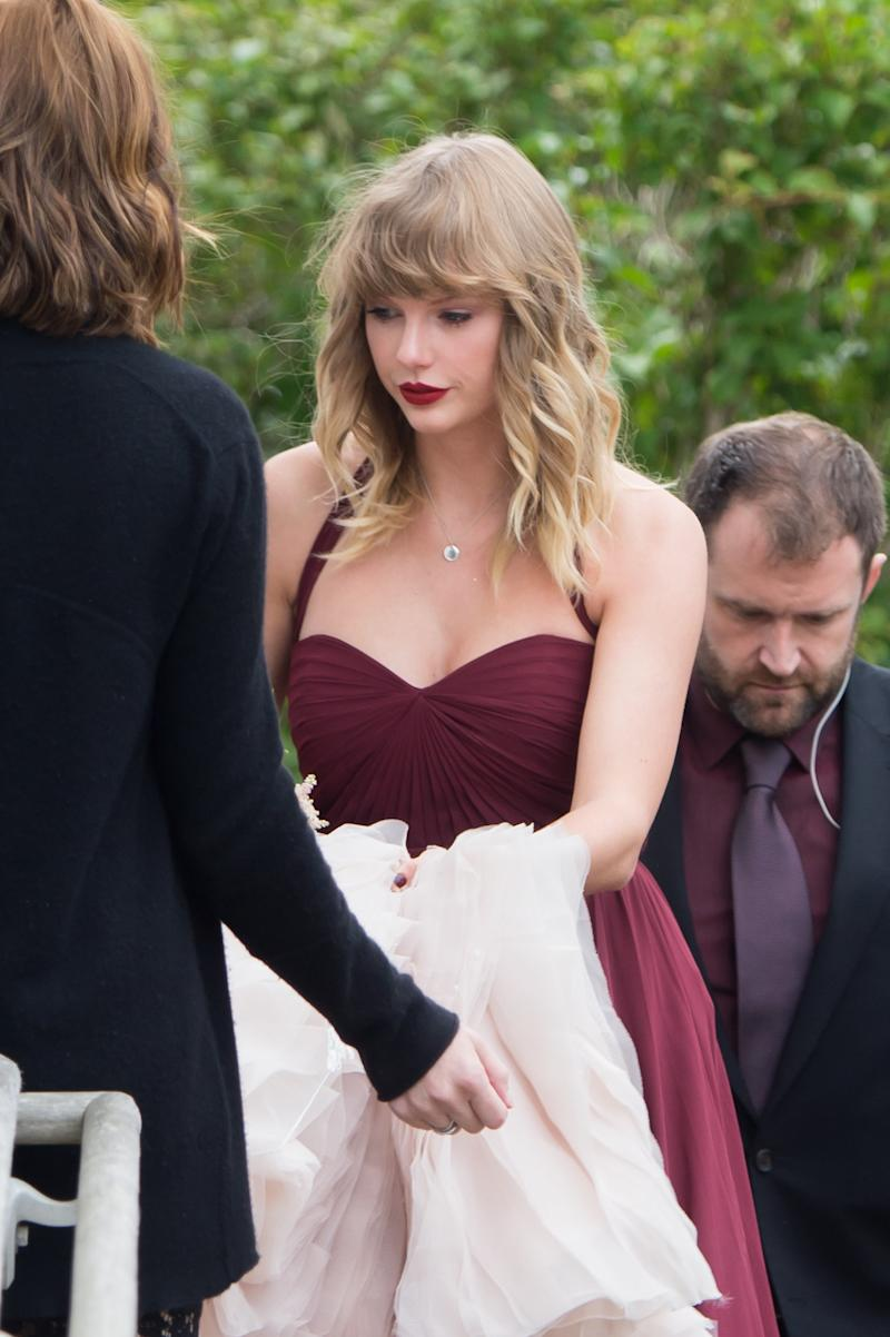 Taylor Swift is seen carrying the back of her BFF Abigail's wedding dress as they arrive at a church in Martha's Vineyard.  (Splash News)